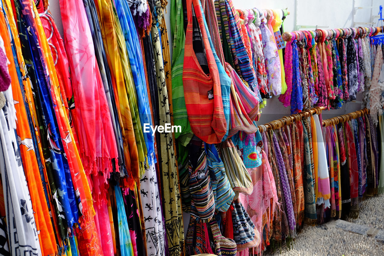 Colorful scarfs and bags for sale at market stall