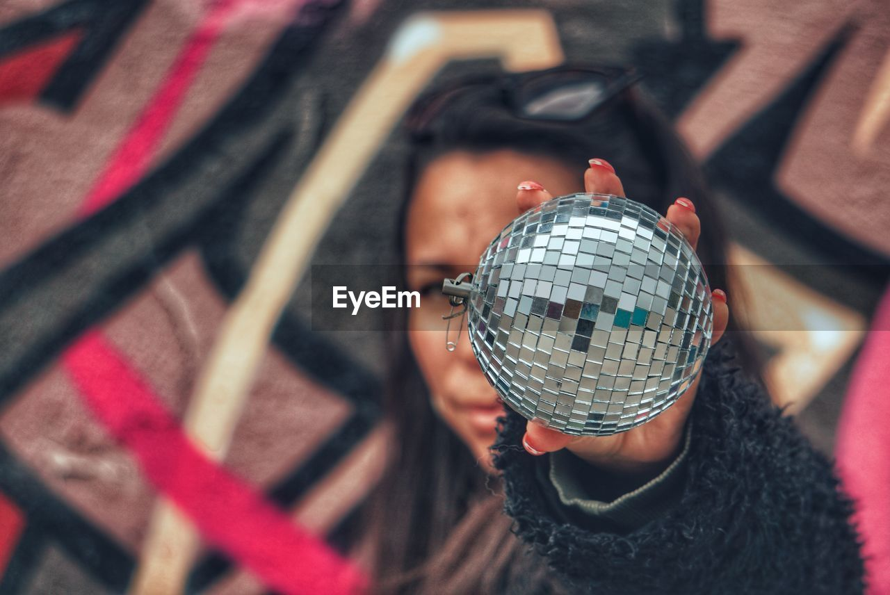 Portrait of woman holding disco ball against face