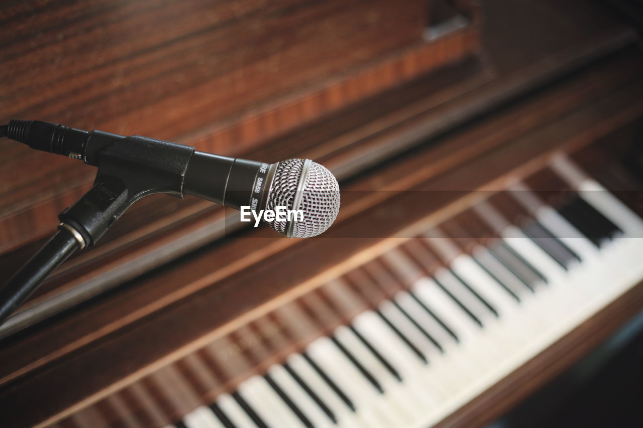Detail Shot Of Microphone Against Piano Keys