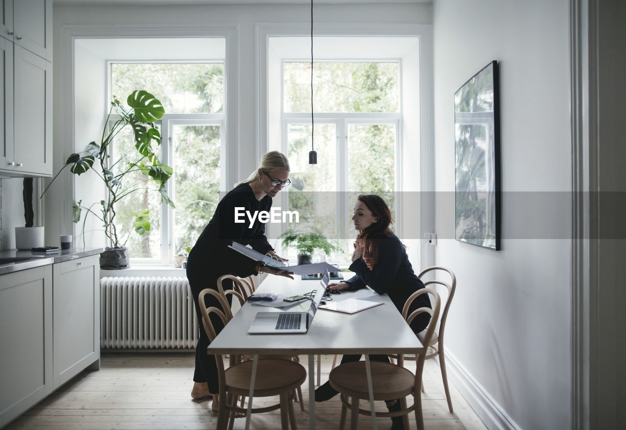 window, table, indoors, adult, two people, women, men, real people, communication, business, sitting, day, males, people, standing, togetherness, cooperation, office, teamwork, working