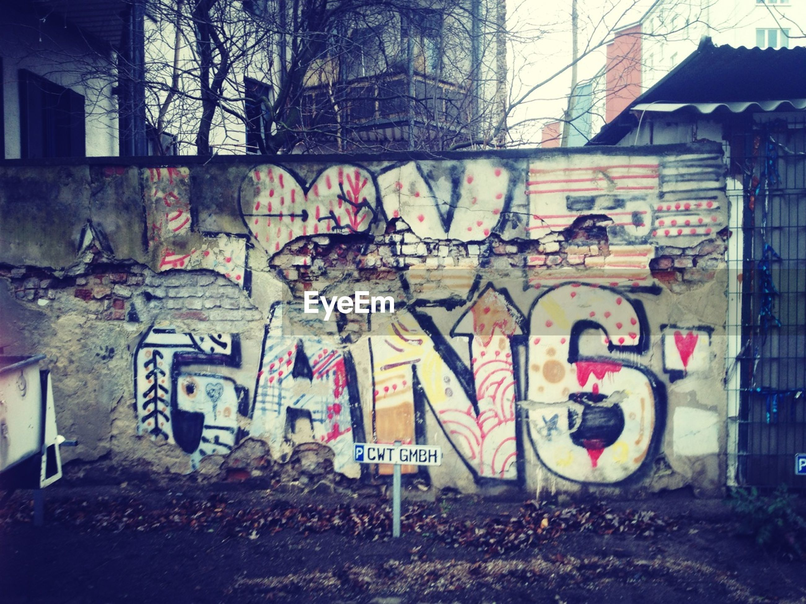architecture, building exterior, built structure, graffiti, text, western script, communication, art, creativity, city, wall - building feature, art and craft, building, street art, road sign, human representation, sign, capital letter, street, outdoors