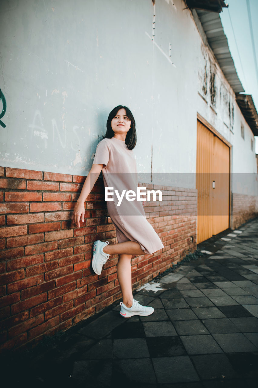 A short hair asian woman in casual clothes is smiling and leaning against the wall