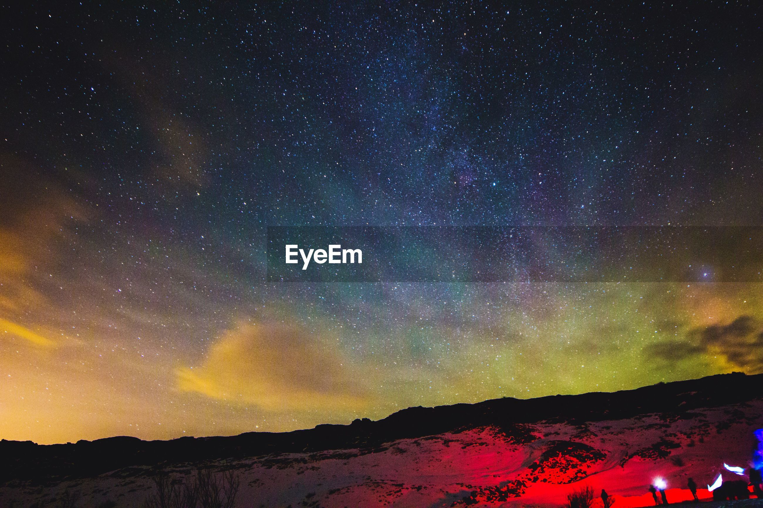 Scenic view of aurora borealis over landscape against sky during winter