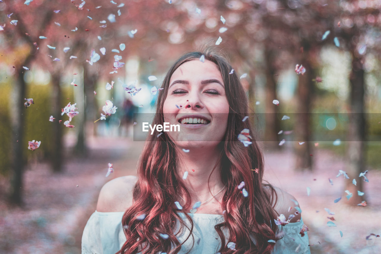 Petals Falling On Smiling Young Woman Against Trees