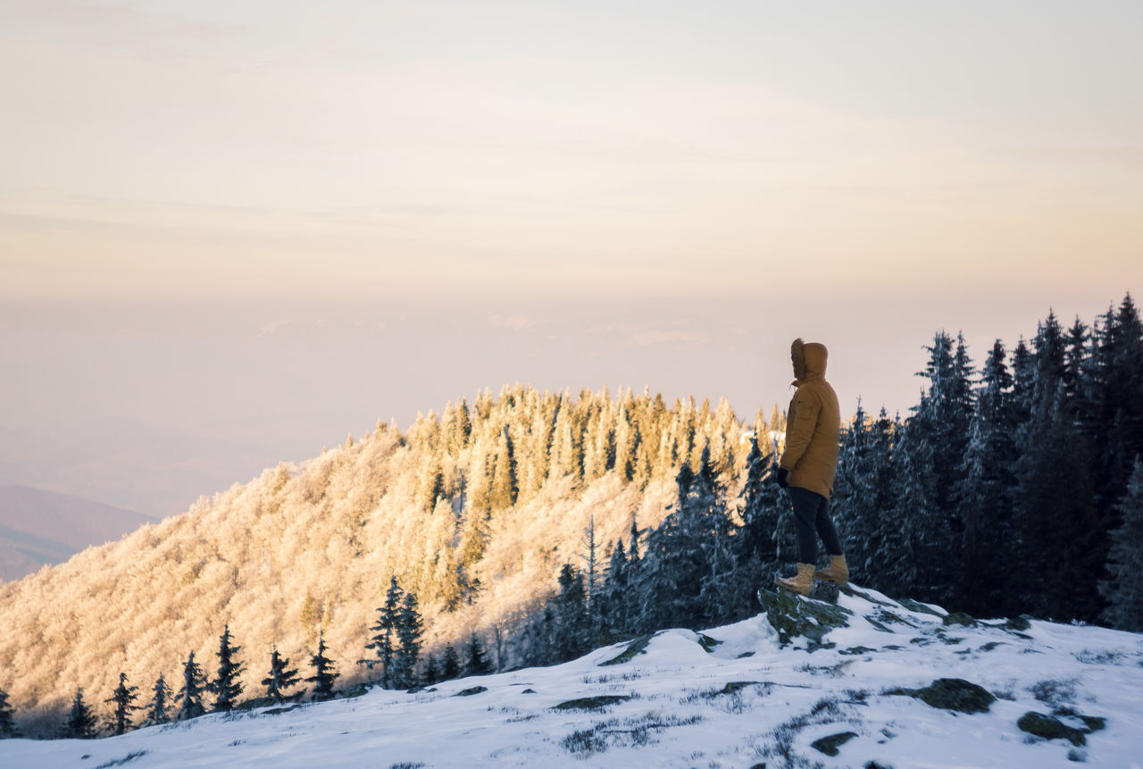 cold temperature, one person, snow, beauty in nature, winter, real people, standing, leisure activity, lifestyles, sky, full length, scenics - nature, mountain, rear view, nature, adventure, tranquil scene, tree, looking at view, outdoors, warm clothing