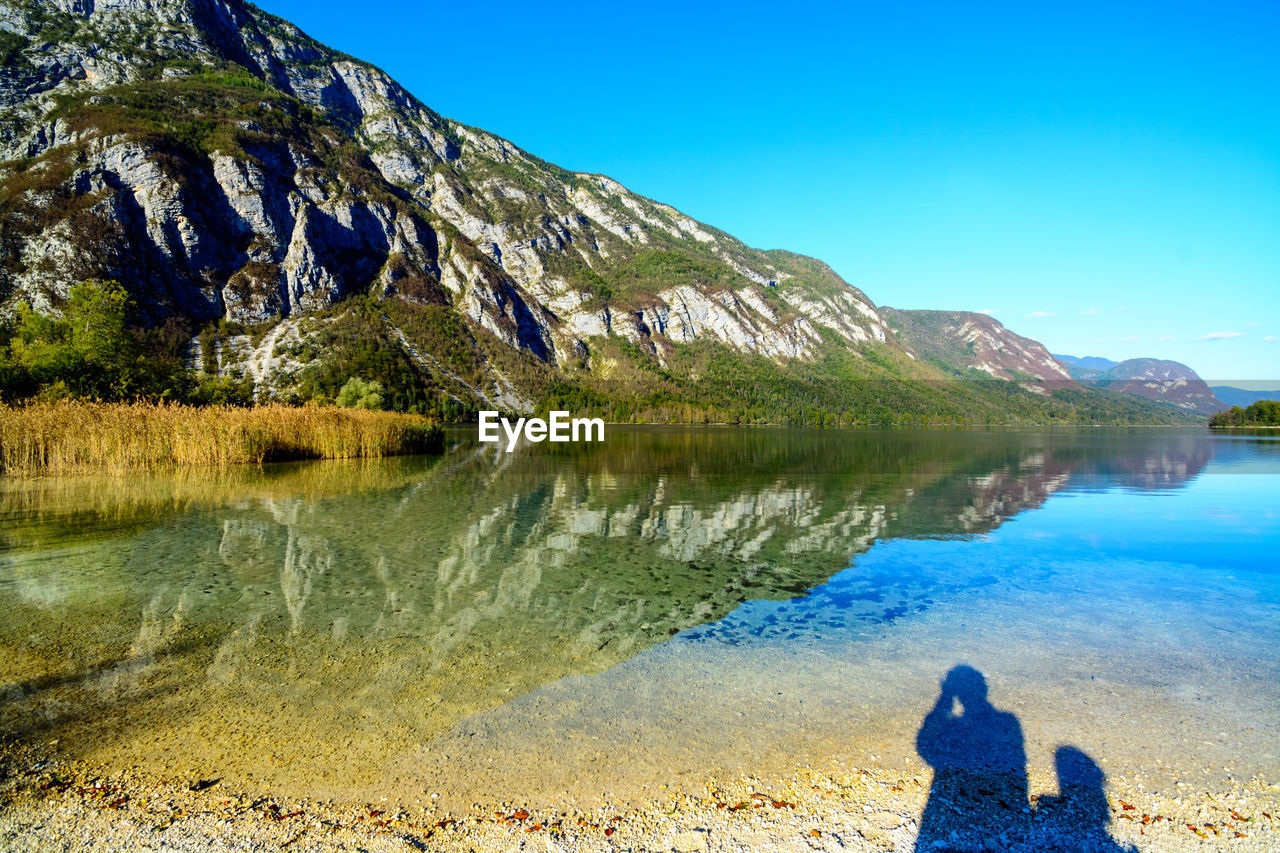 water, beauty in nature, scenics - nature, mountain, lake, real people, tranquility, leisure activity, nature, non-urban scene, blue, tranquil scene, sky, reflection, lifestyles, rear view, day, one person, clear sky, mountain range, outdoors, looking at view
