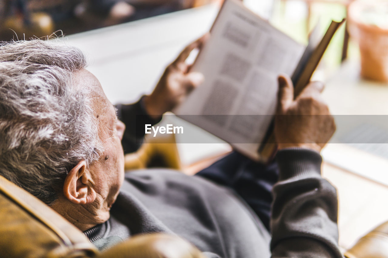 one person, activity, real people, men, book, indoors, publication, selective focus, males, reading, sitting, adult, leisure activity, senior adult, relaxation, lifestyles, holding, senior men, home interior, mature men, studying