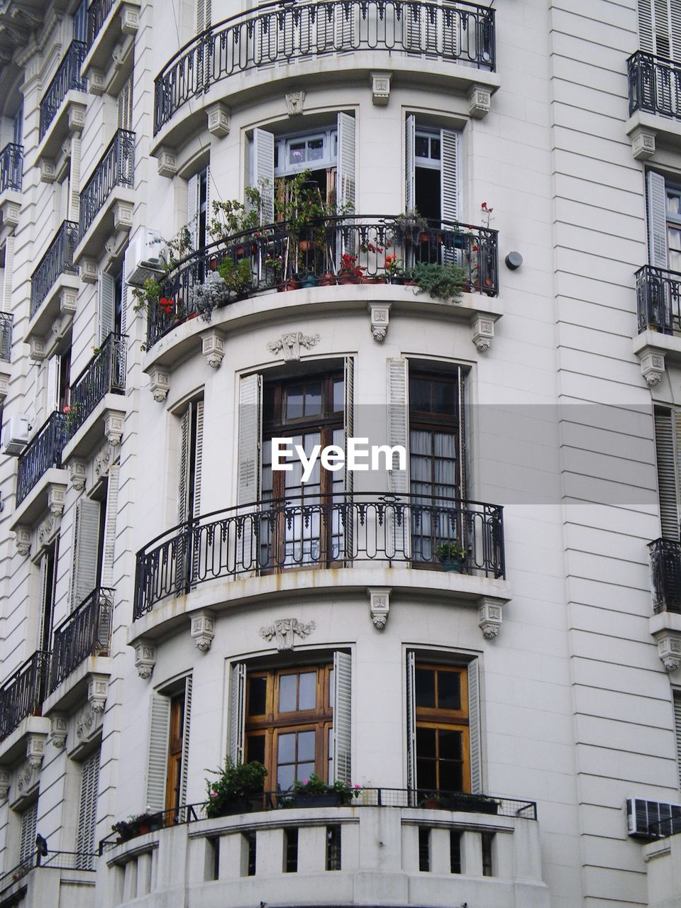 building exterior, architecture, built structure, window, building, residential district, balcony, city, low angle view, no people, day, outdoors, apartment, nature, plant, house, glass - material, side by side, city life, arch, window box