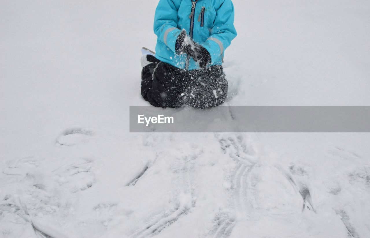 Low section of boy kneeling on snow field during winter