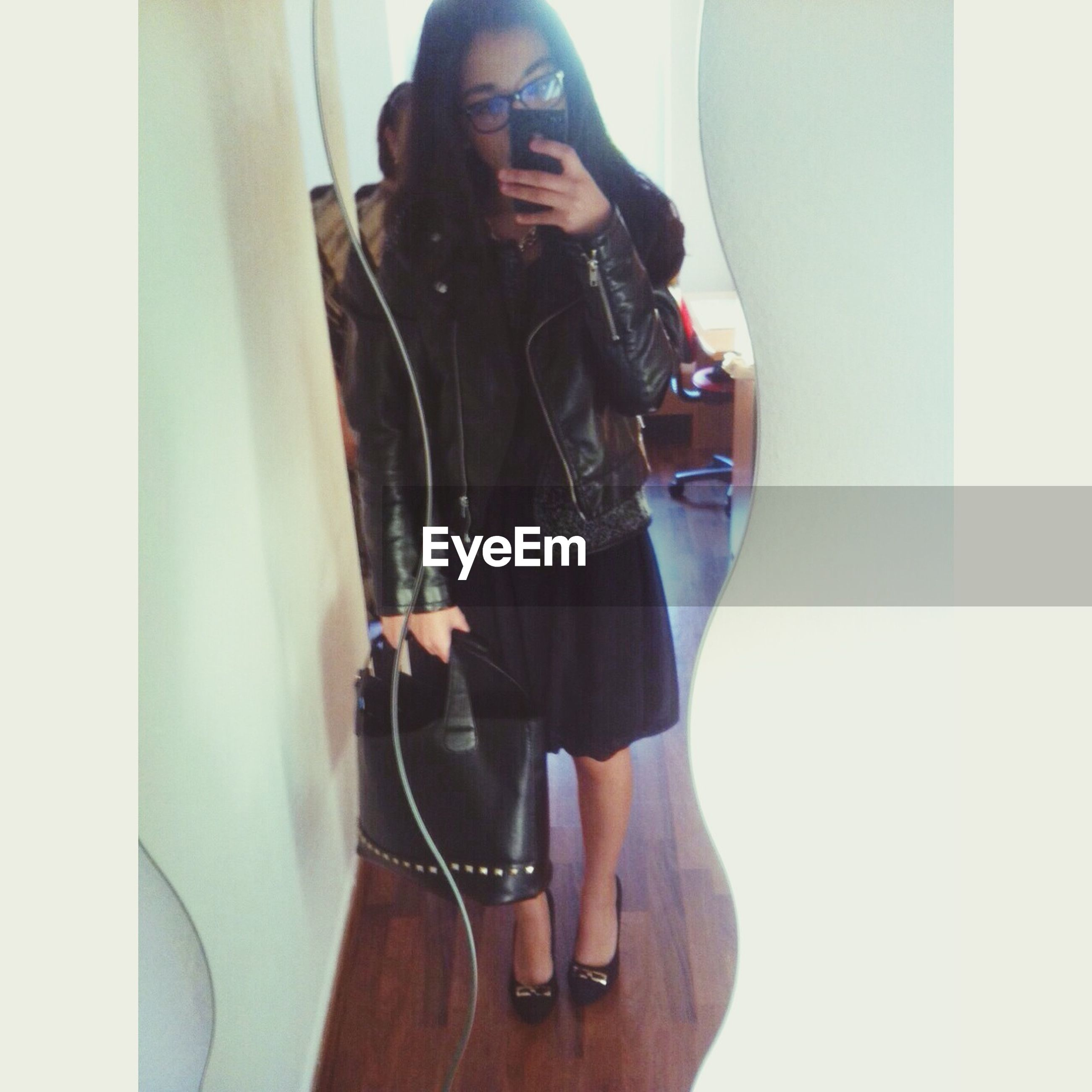 indoors, young adult, lifestyles, casual clothing, leisure activity, young women, standing, front view, person, full length, three quarter length, technology, holding, photography themes, wireless technology, photographing, fashion