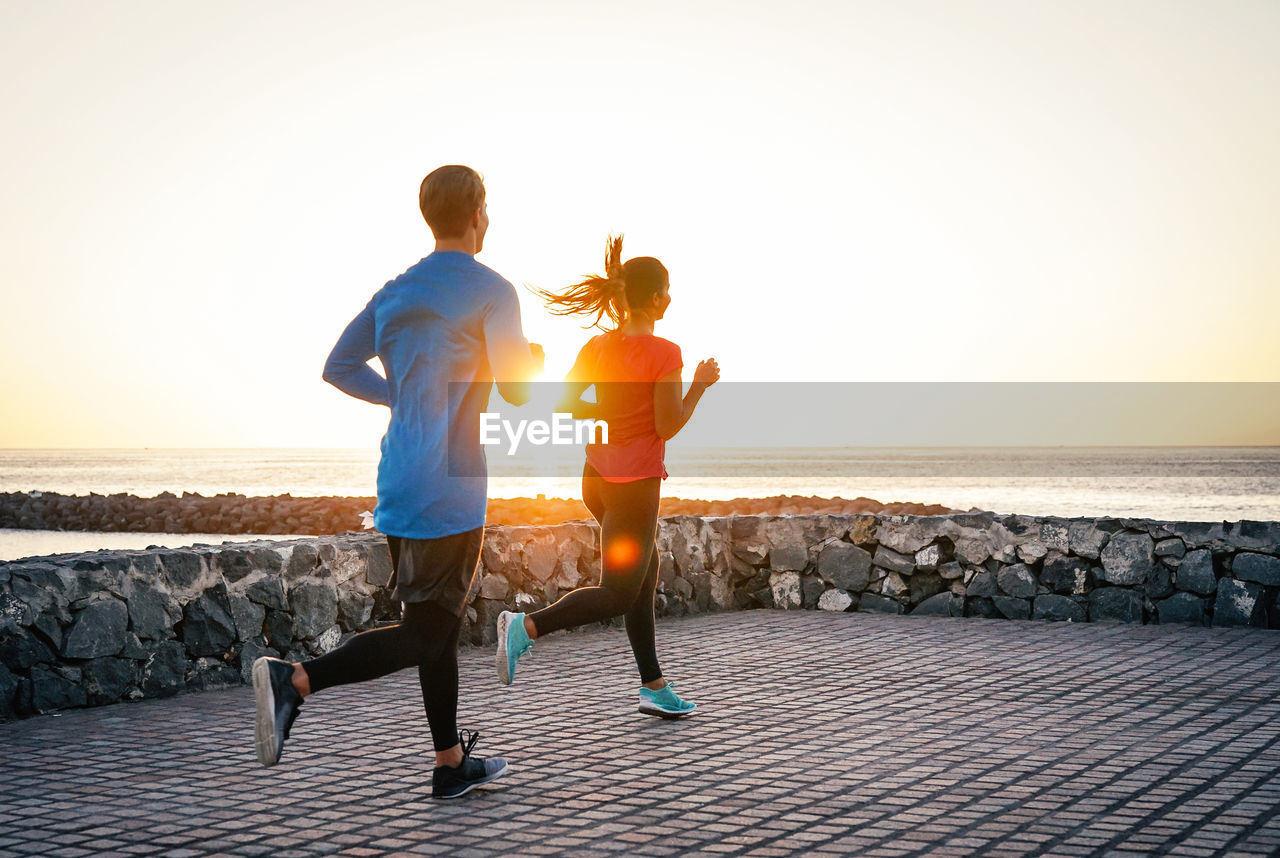 Couple jogging on promenade against clear sky during sunset