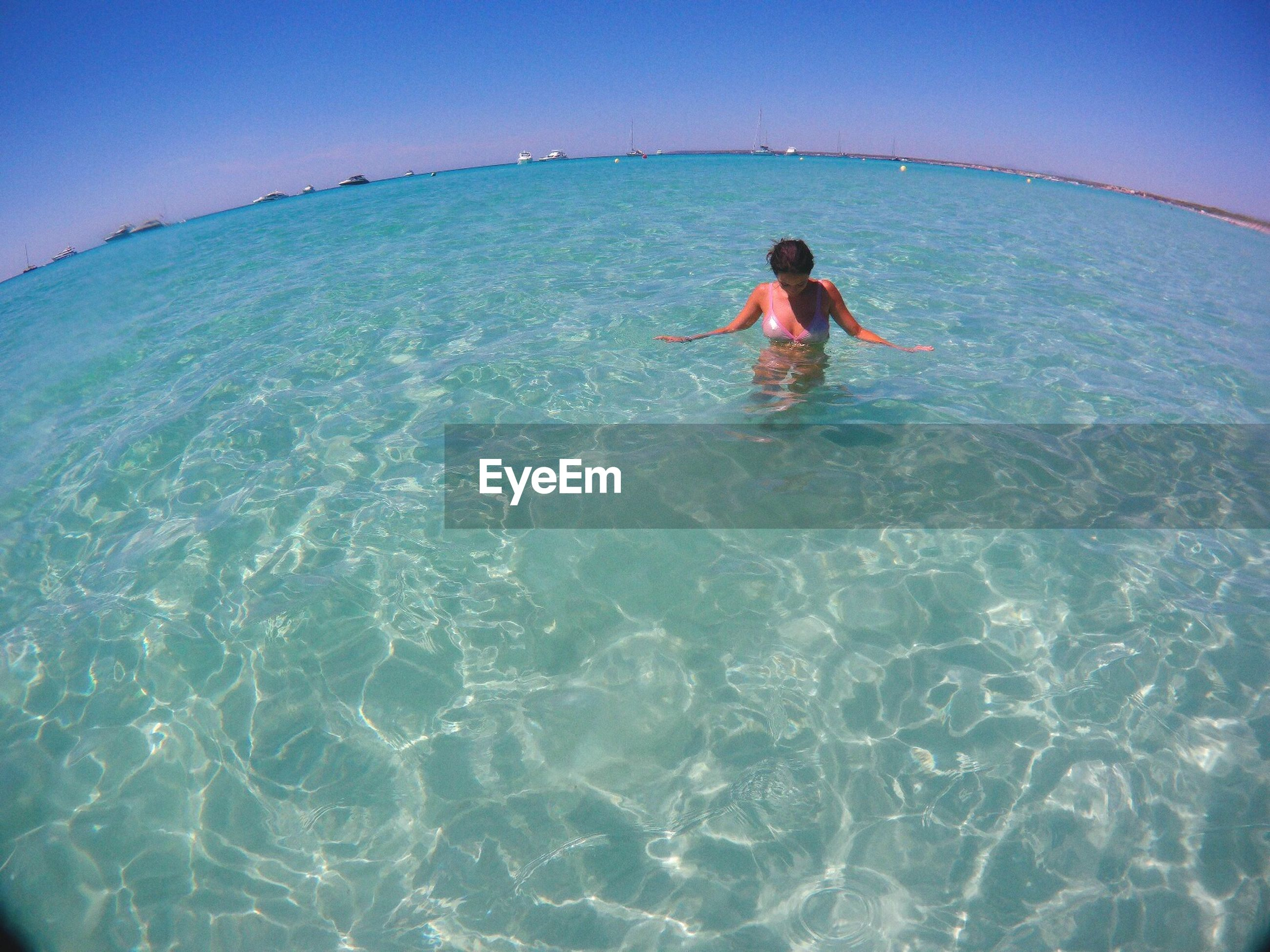 sea, real people, leisure activity, lifestyles, one person, vacations, water, waterfront, day, nature, outdoors, beauty in nature, clear sky, young adult, young women, swimming, ankle deep in water, sky, people