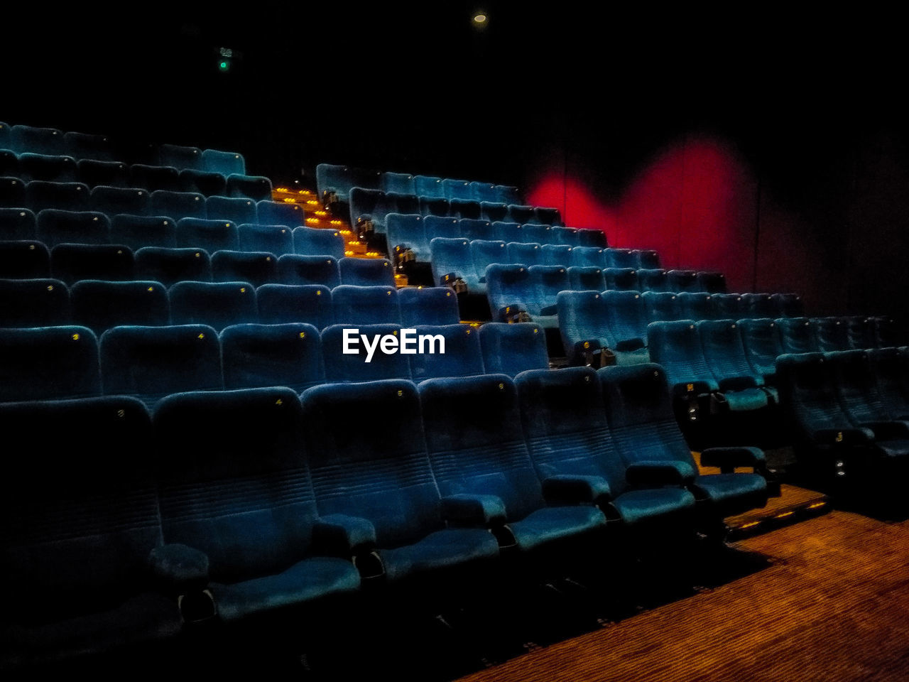 in a row, seat, arts culture and entertainment, indoors, empty, no people, movie theater, absence, repetition, side by side, theater, illuminated, chair, large group of objects, red, auditorium, order, arrangement, architecture, sport, nightlife