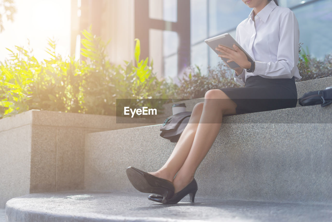 Low section of businesswoman using digital tablet while sitting against office building