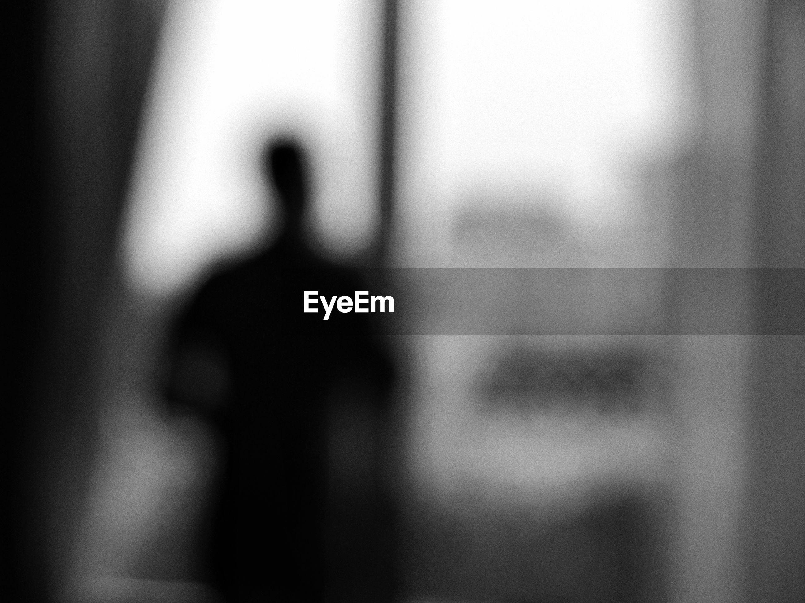 Defocused image of man standing by window