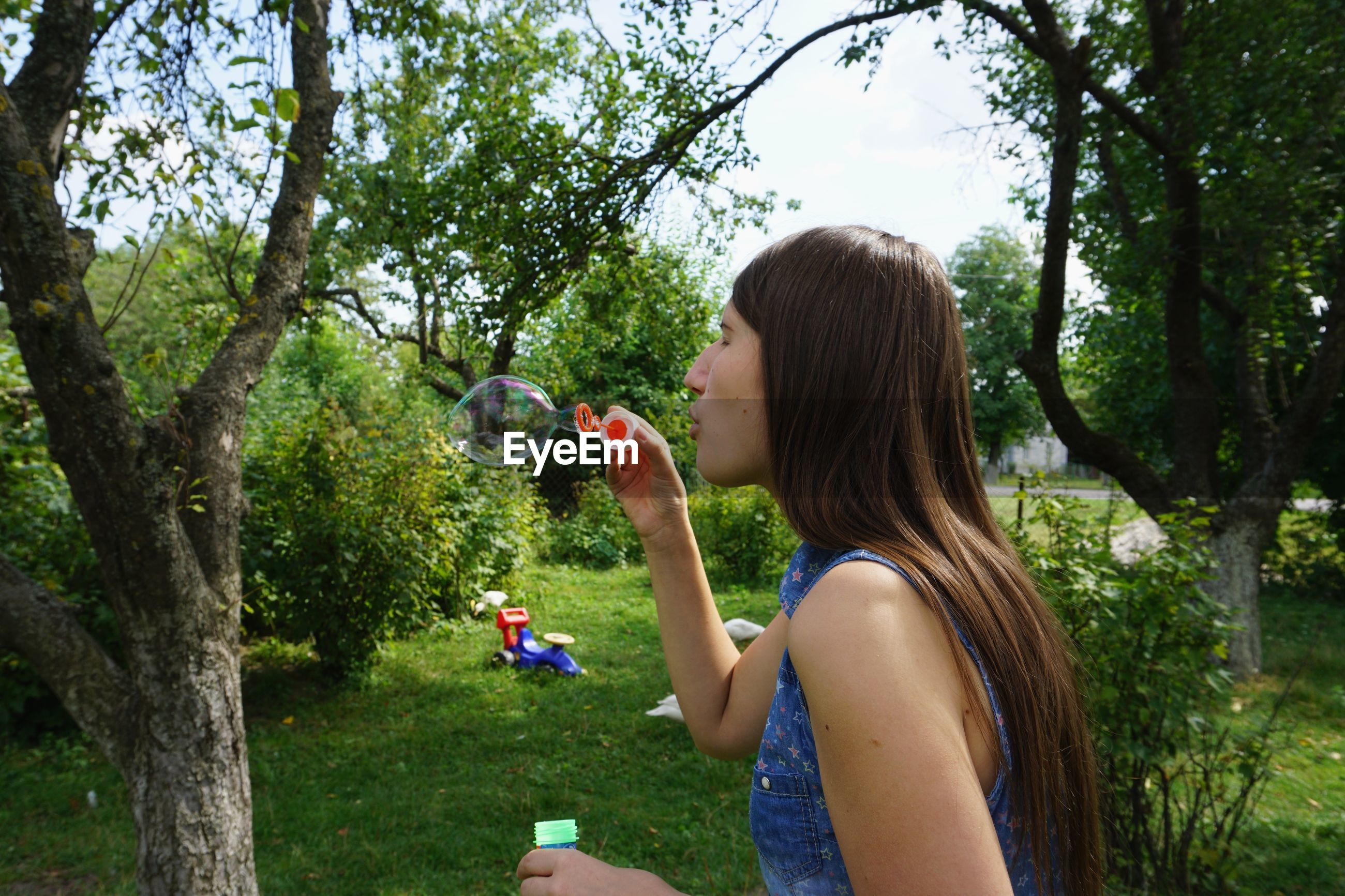 Side view of young woman blowing bubbles in back yard