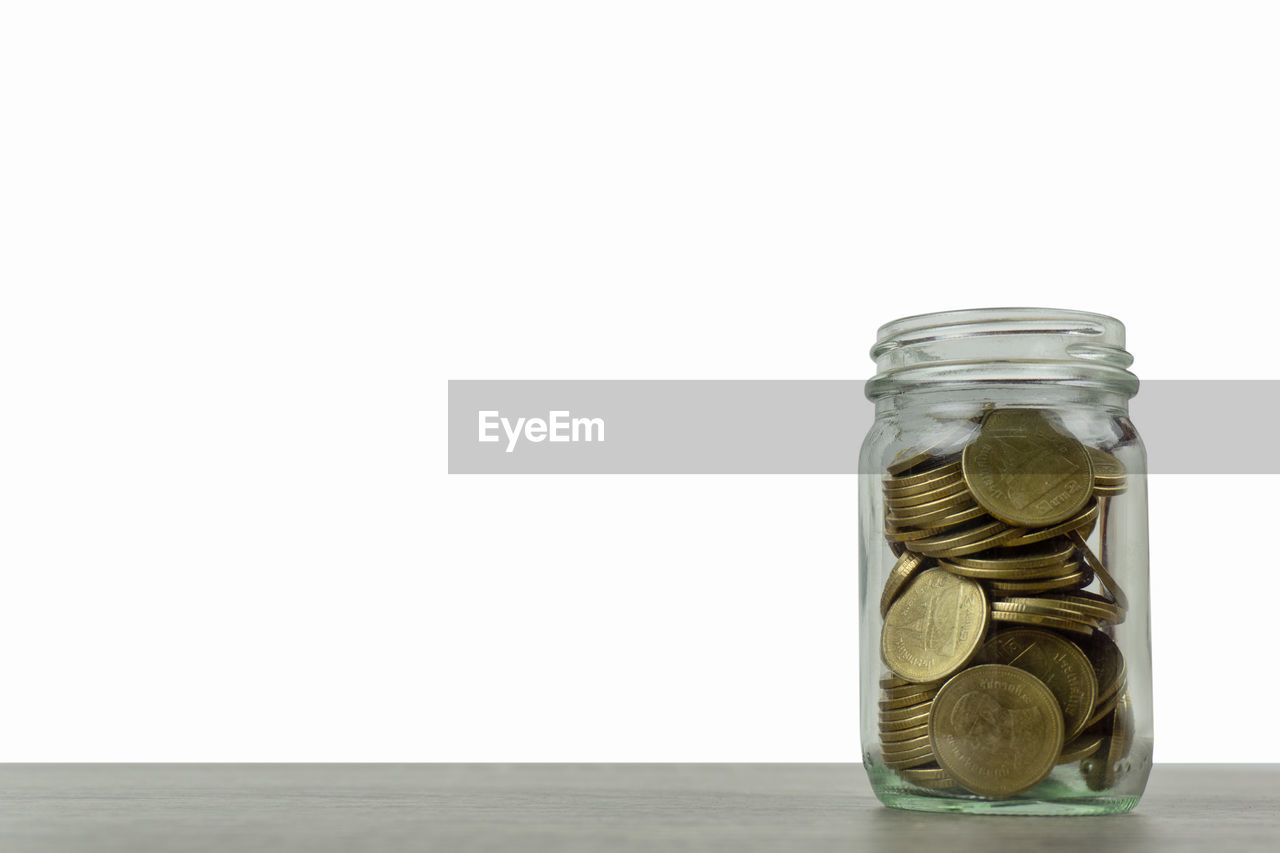 Close-up of coins in jar on table against white background