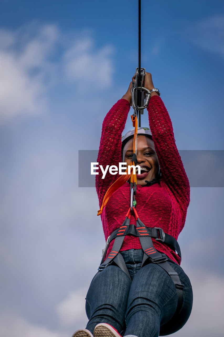 Low angle view of woman hanging on rope against sky