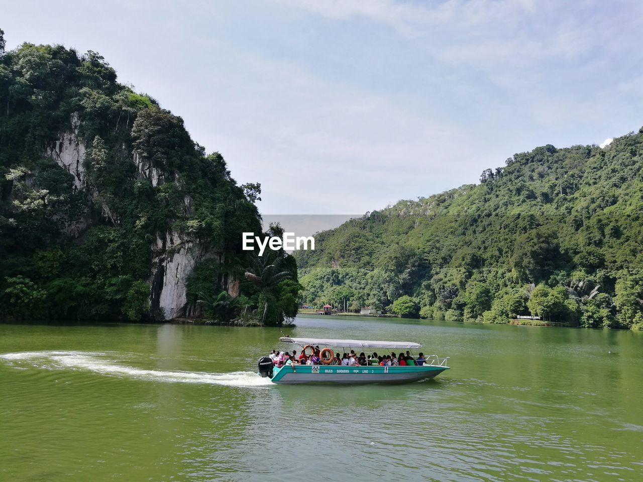 water, nautical vessel, transportation, mode of transportation, waterfront, tree, beauty in nature, plant, day, travel, nature, mountain, scenics - nature, group of people, river, sky, real people, rock, green color, outdoors