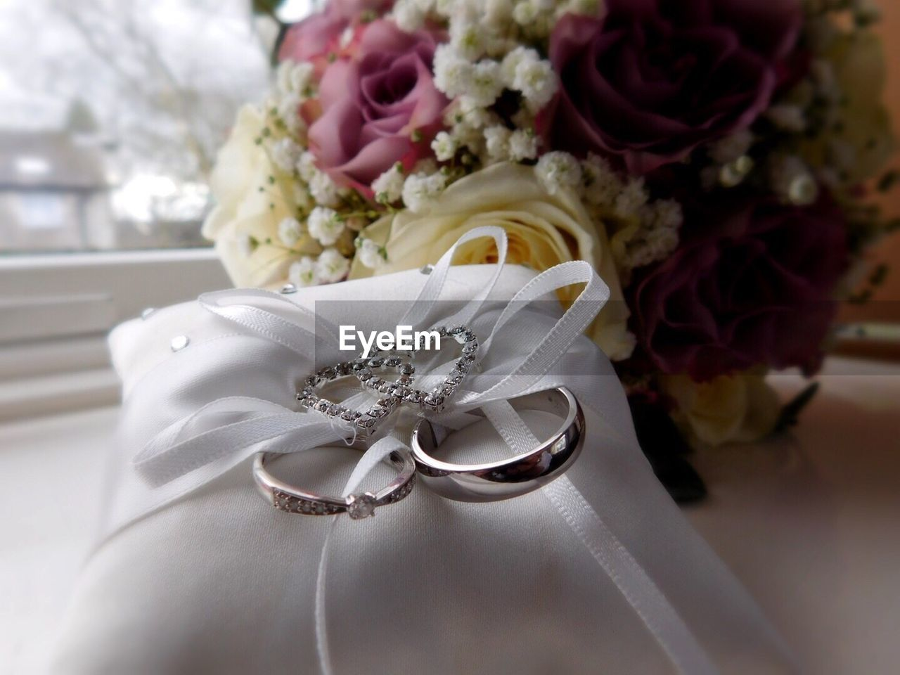flowering plant, flower, celebration, plant, wedding, rose, event, beauty in nature, rose - flower, close-up, jewelry, flower arrangement, freshness, bouquet, white color, ring, flower head, life events, nature, wedding ring, no people, wedding ceremony, personal accessory