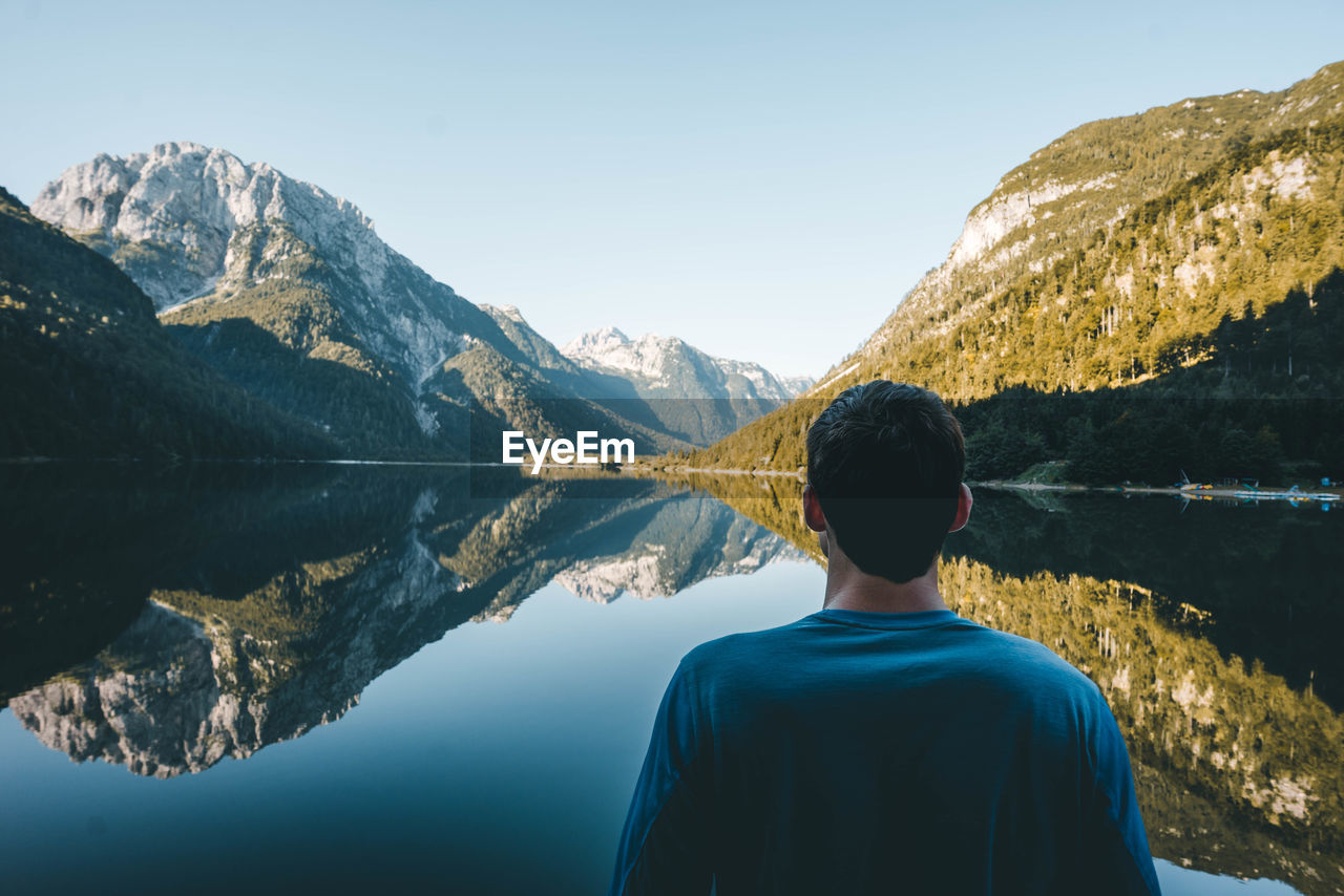 Rear View Of Young Man Looking At Calm Lake By Mountains Against Sky