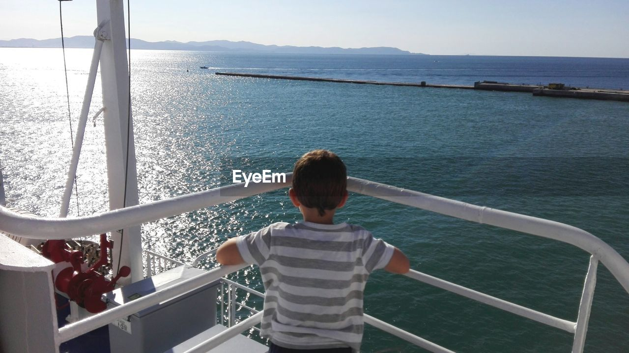water, sea, railing, rear view, real people, beauty in nature, nature, lifestyles, leisure activity, one person, scenics - nature, sky, nautical vessel, day, men, standing, women, child, boys, looking at view, outdoors, horizon over water