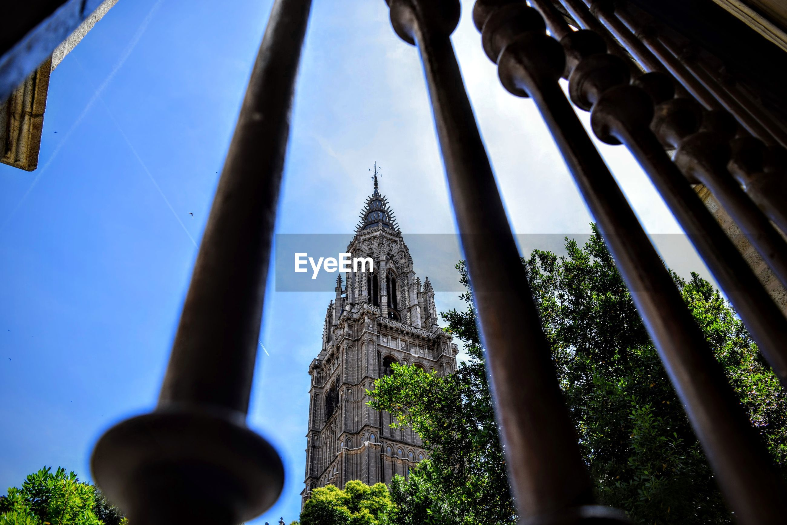 Low angle view of tower seen through railing against blue sky
