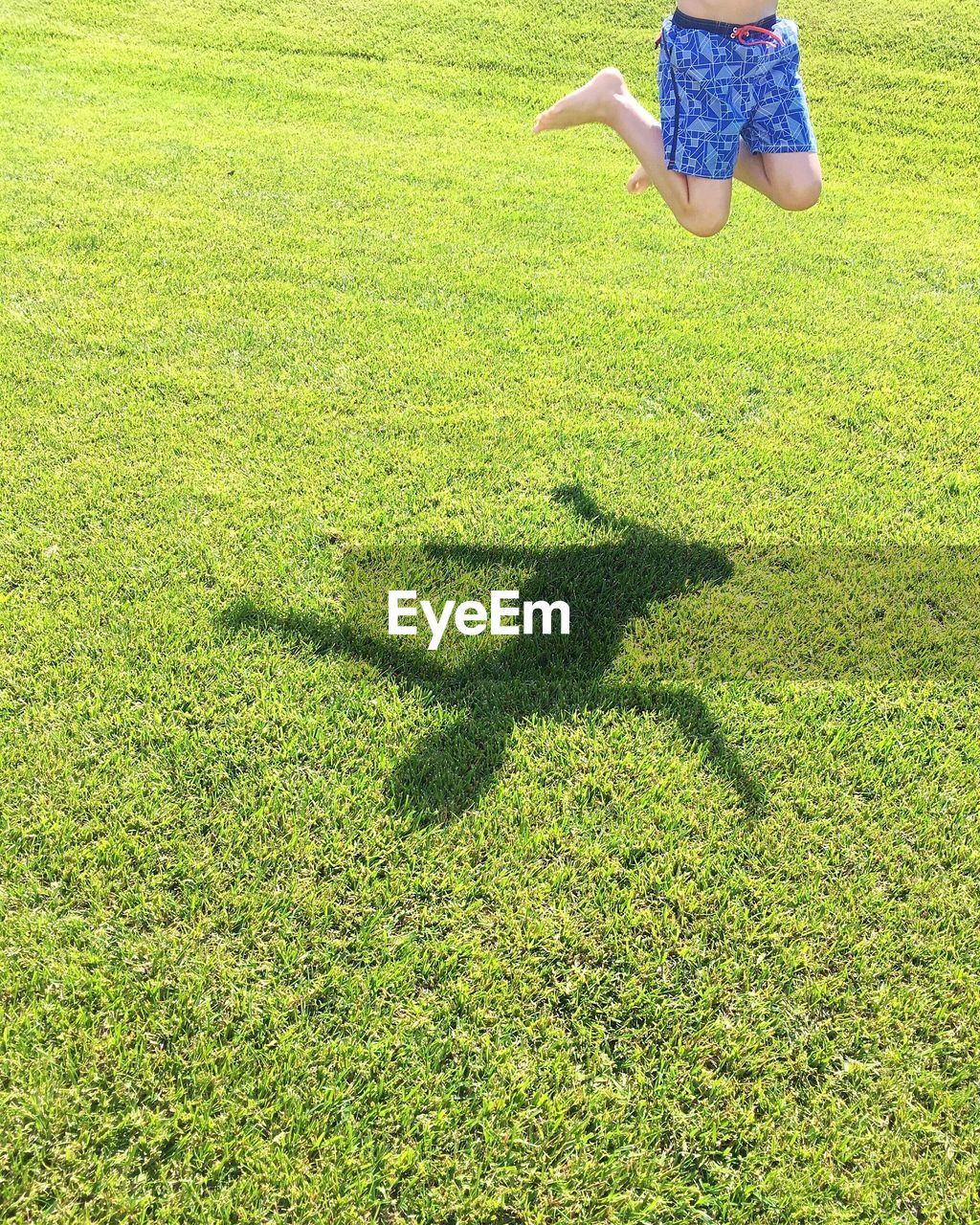 Low section of boy jumping on field