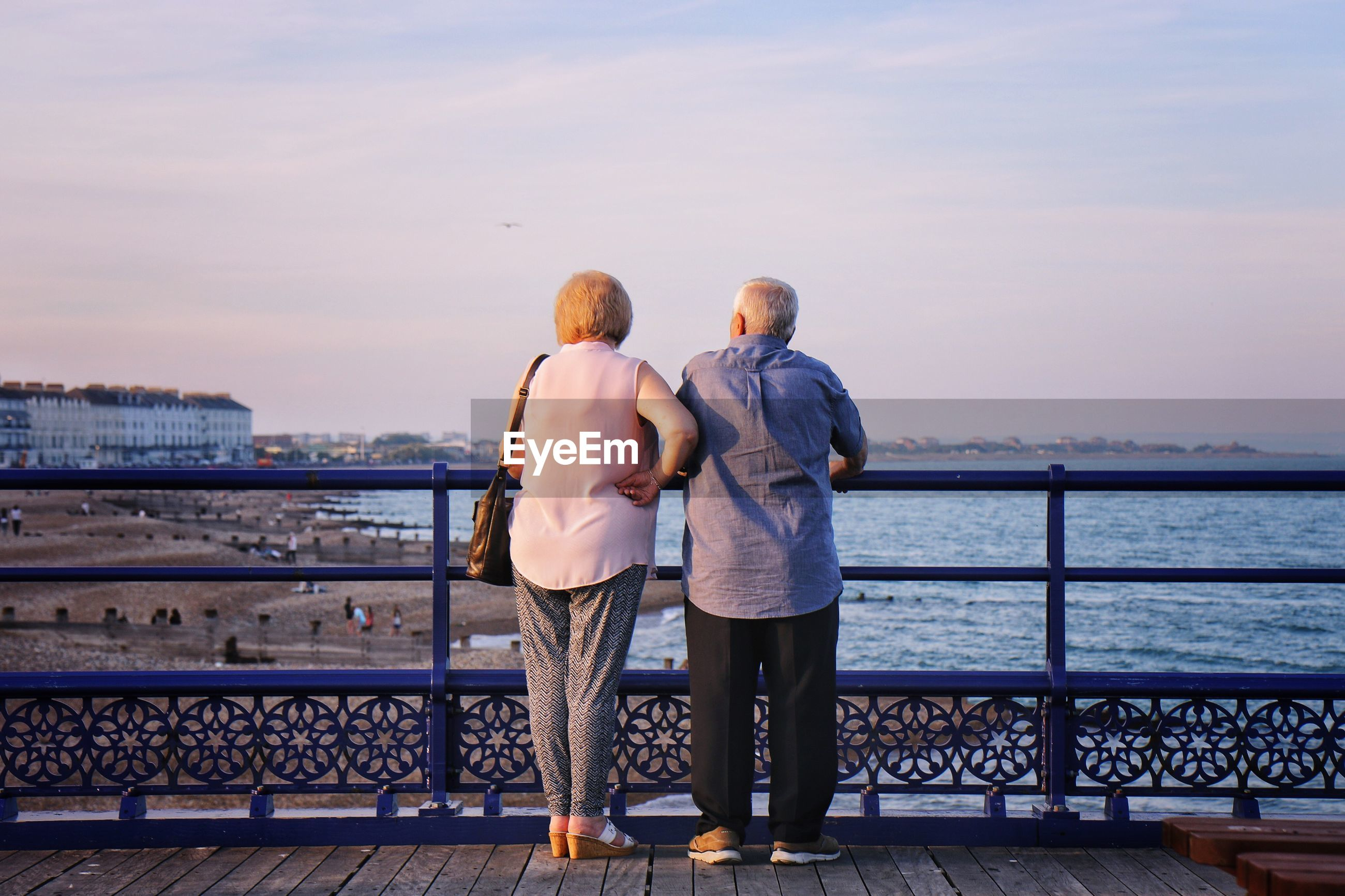 Rear view of couple looking at sea while standing by railing against sky during sunset