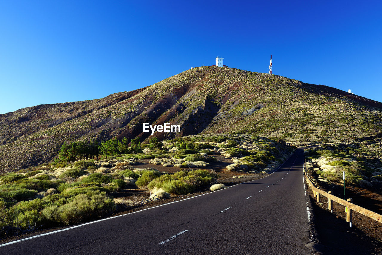 Road leading towards green mountain against clear blue sky
