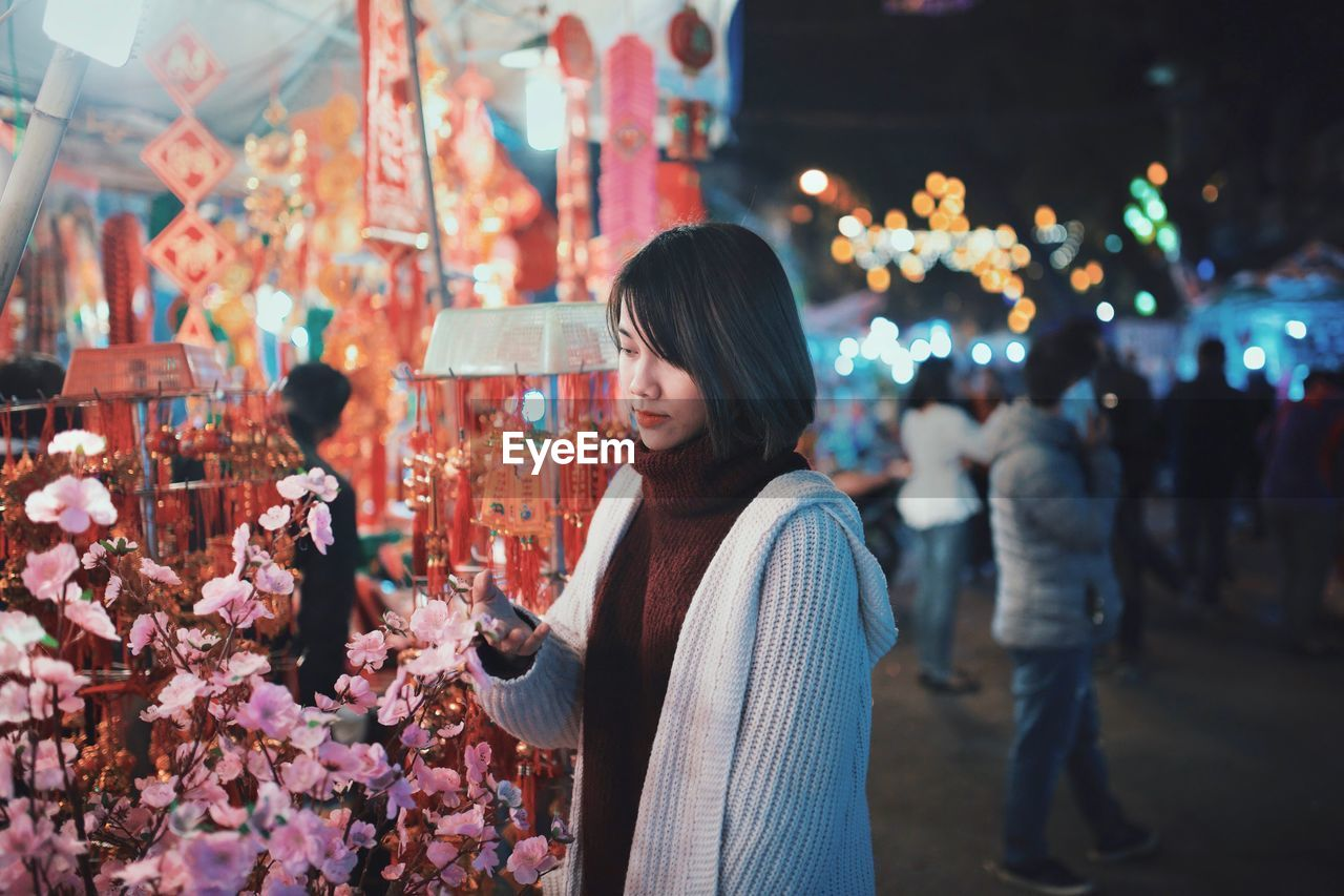Young Woman Touching Flowers In Market At Night