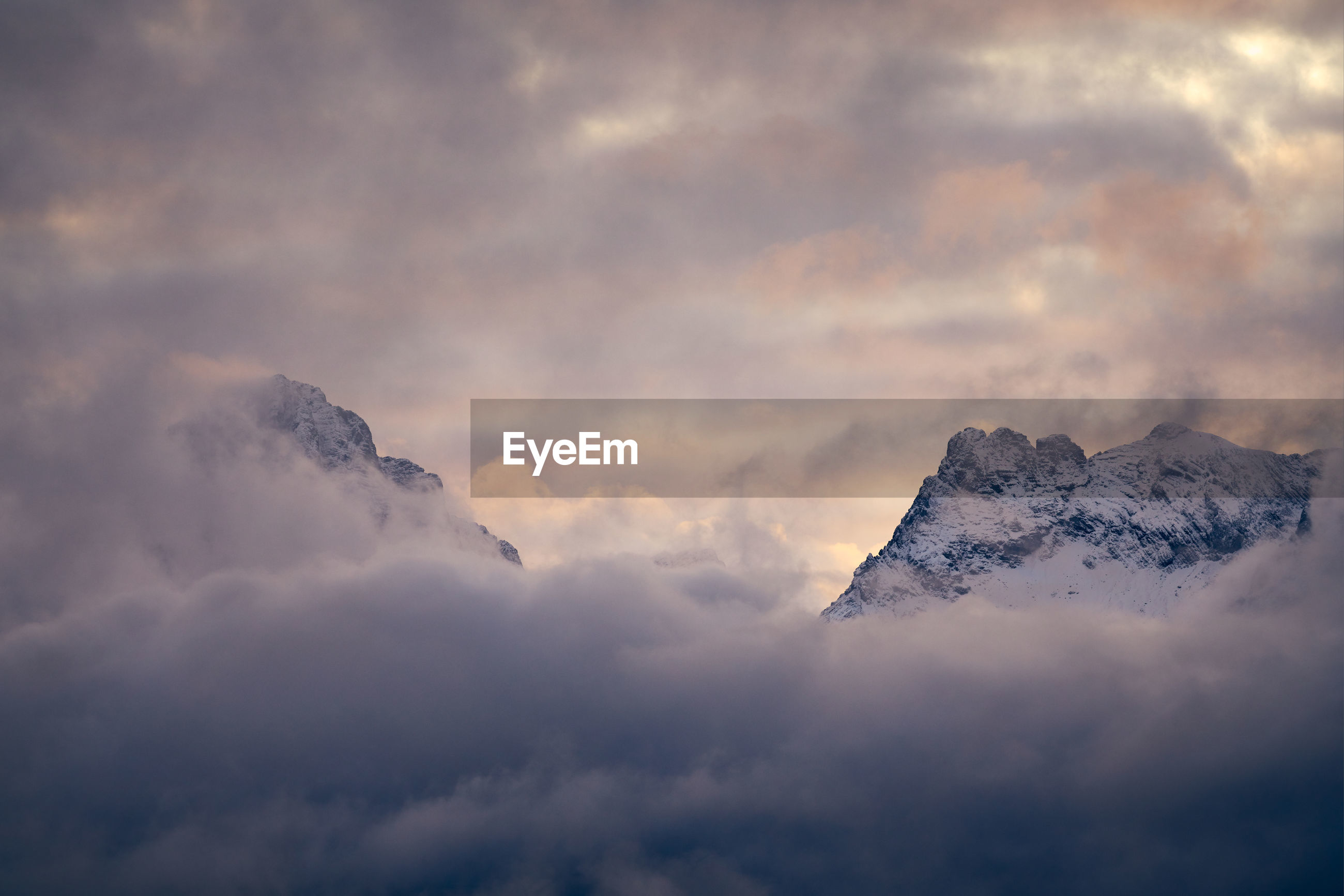 LOW ANGLE VIEW OF SNOWCAPPED MOUNTAIN AGAINST CLOUDY SKY