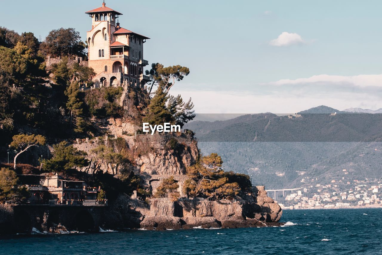 architecture, mountain, building exterior, built structure, water, building, sky, sea, nature, waterfront, tree, rock, religion, beauty in nature, place of worship, day, belief, spirituality, mountain range, no people, outdoors, formation