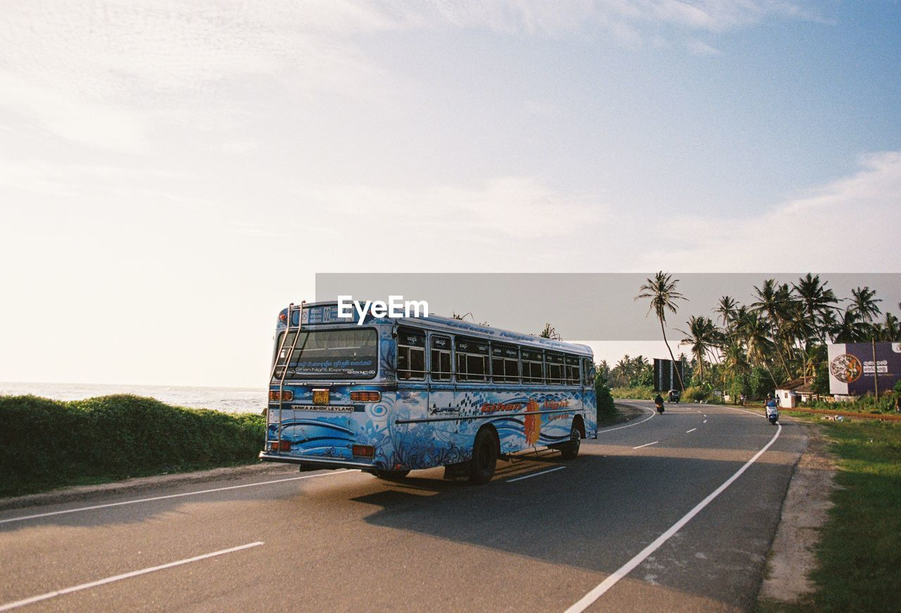 transportation, mode of transport, road, sky, day, outdoors, land vehicle, tree, cloud - sky, real people, one person, men, people