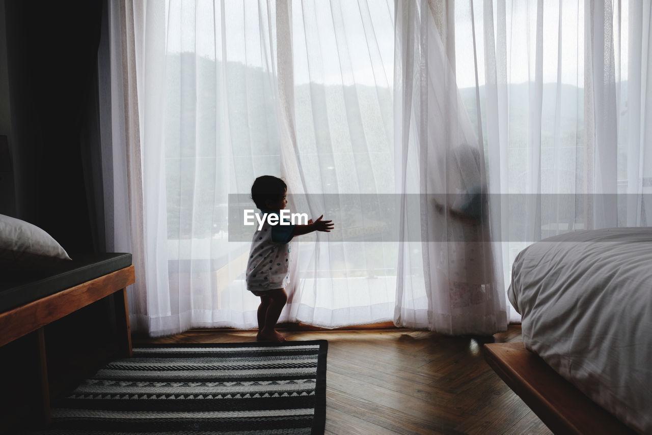 REAR VIEW OF BOY STANDING BY WINDOW