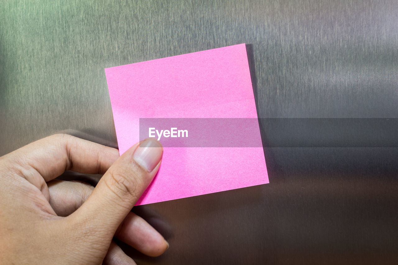 Close-up of human hand touching adhesive note