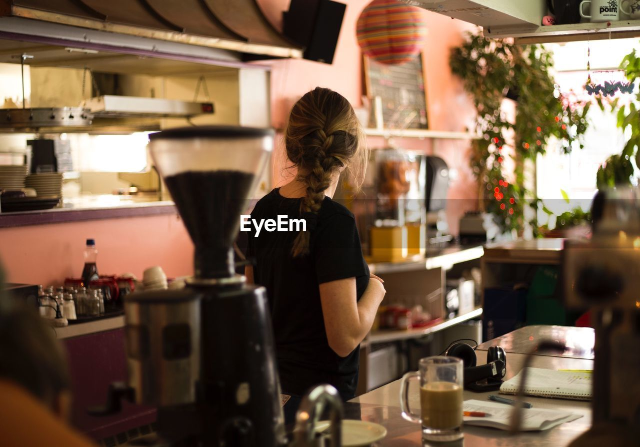 Rear View Of Woman Standing In Cafe