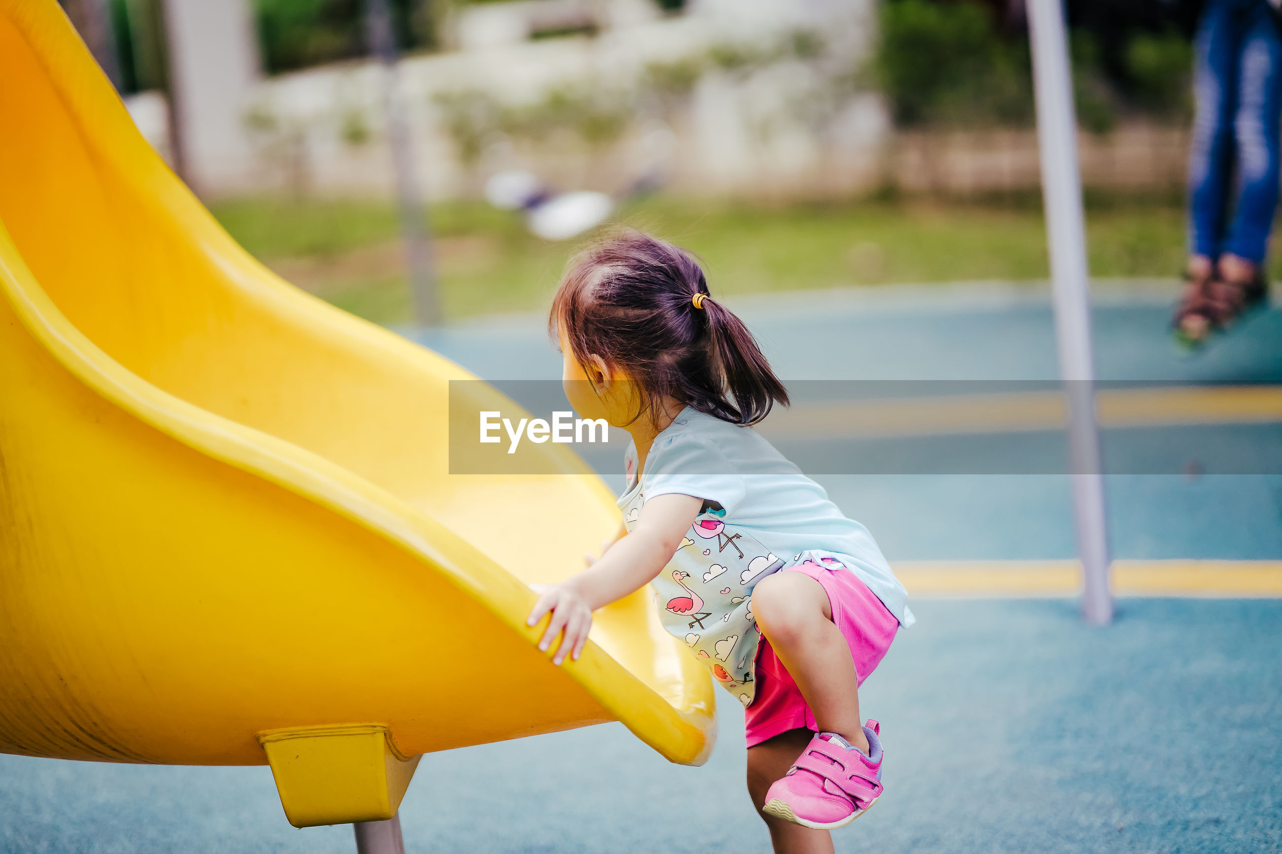 Side view of girl playing on slide