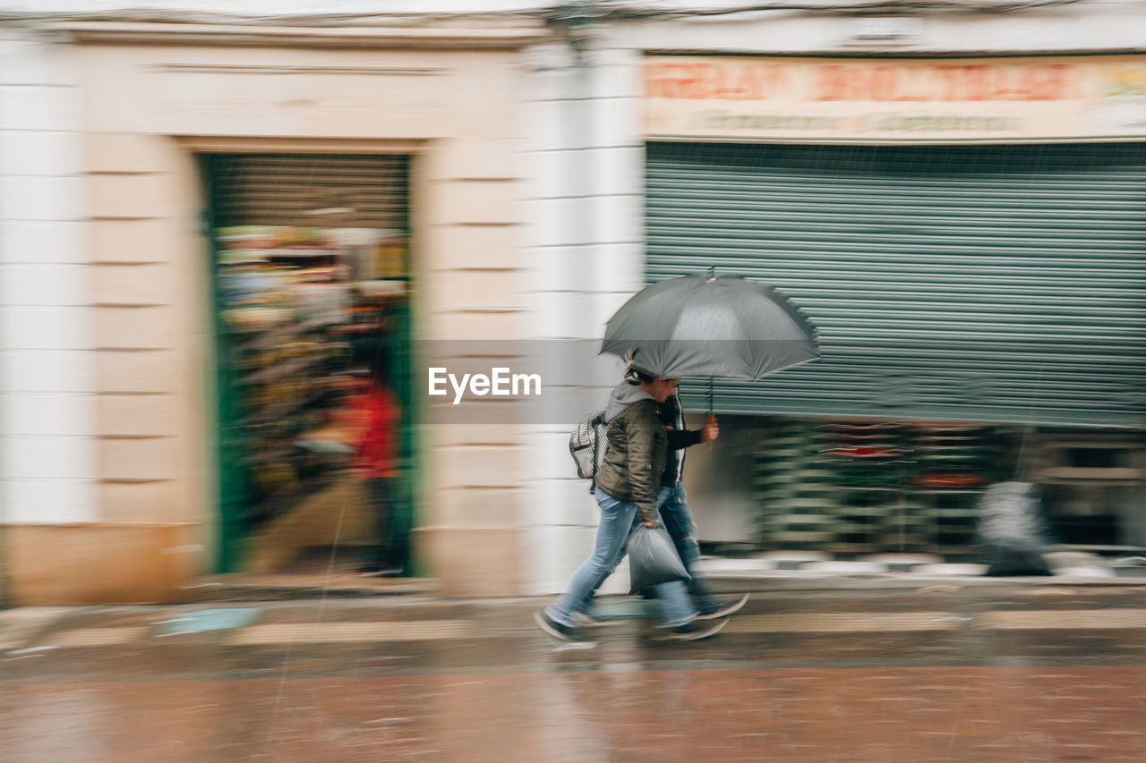 blurred motion, building exterior, motion, architecture, built structure, full length, umbrella, real people, one person, walking, day, city, protection, street, men, adult, casual clothing, women, outdoors, rain, rainy season, obscured face