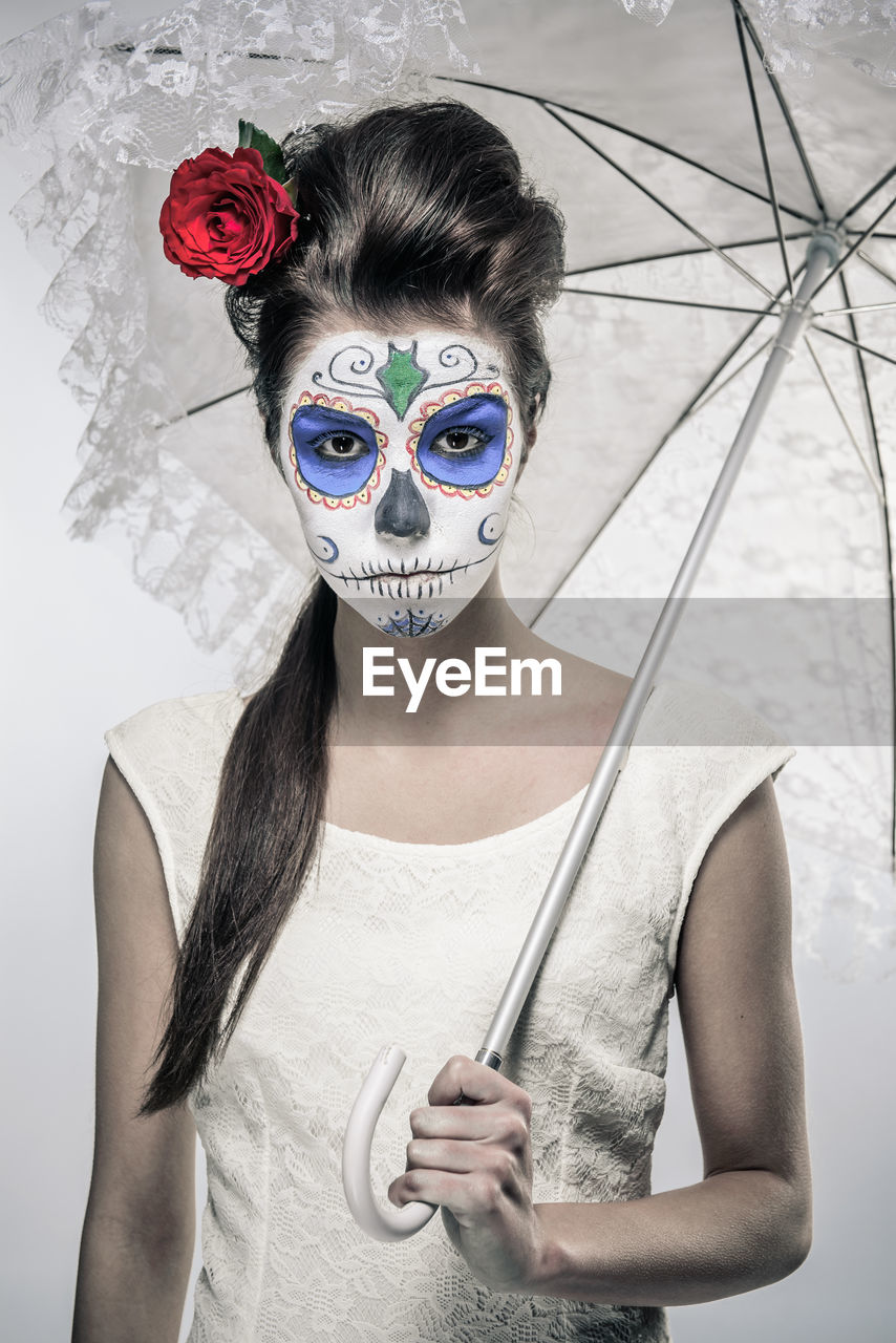 PORTRAIT OF YOUNG WOMAN WEARING MASK HOLDING UMBRELLA STANDING OUTDOORS