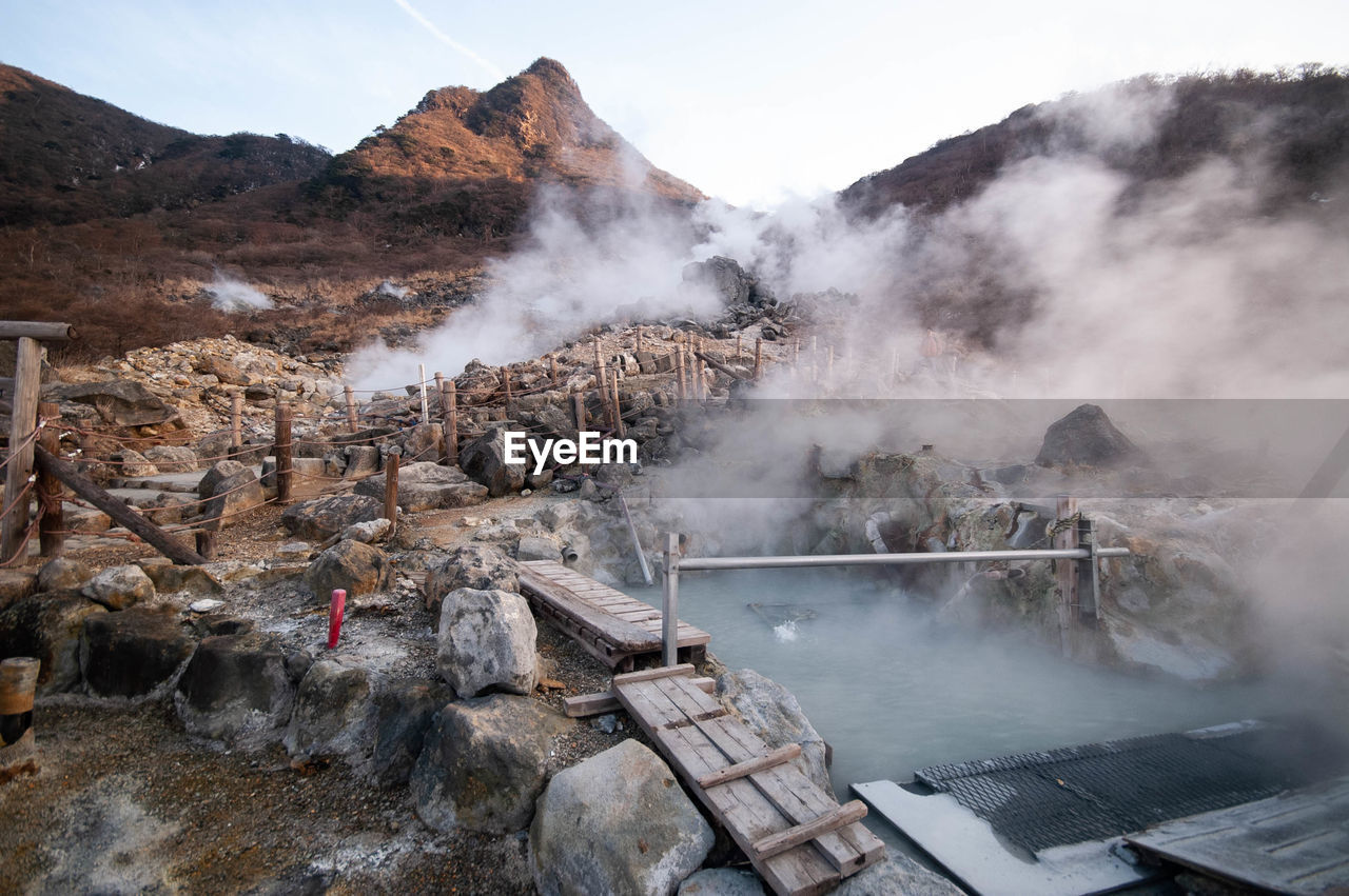 Smoke emitting from hot springs by mountains