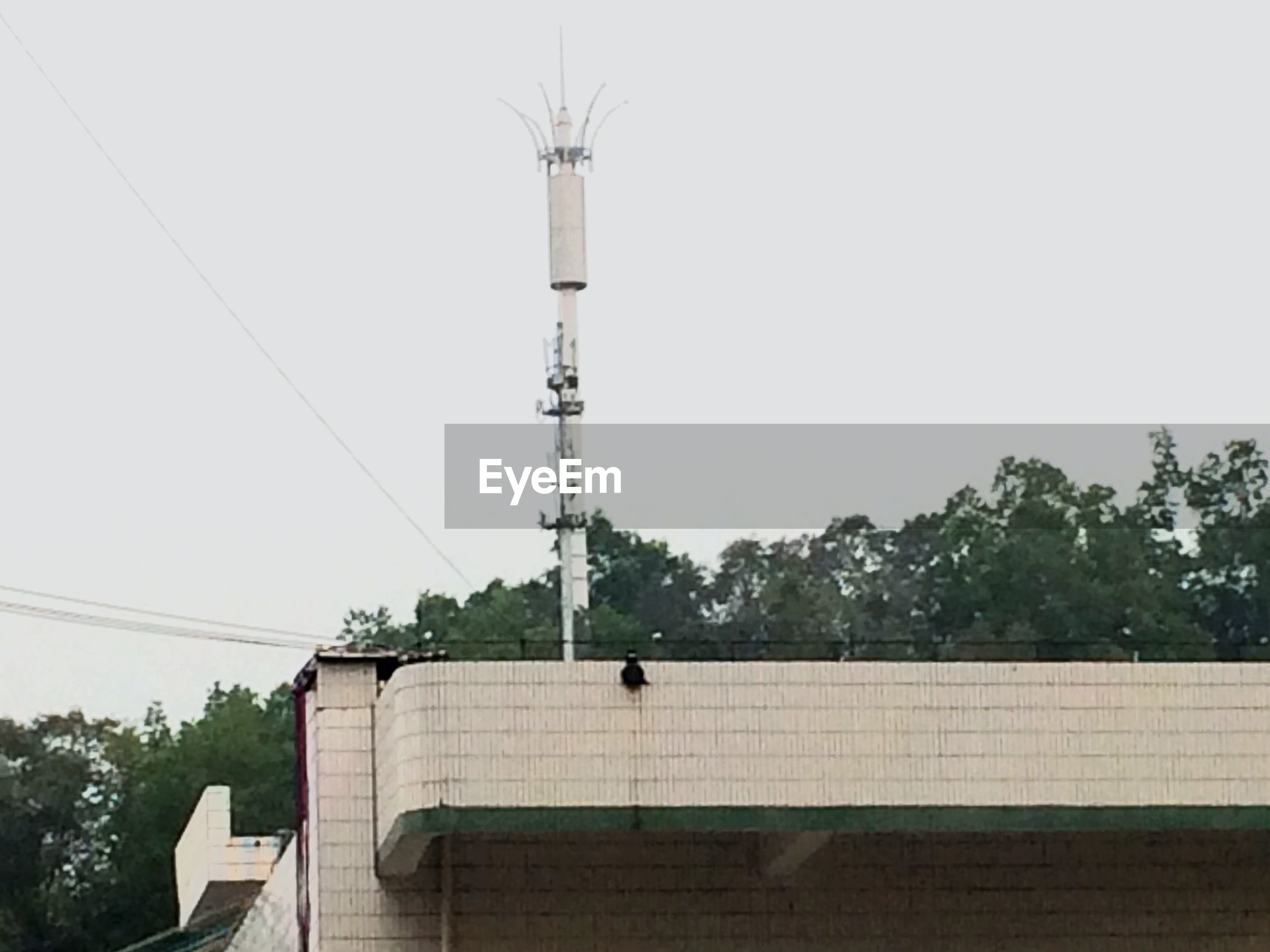 architecture, built structure, clear sky, building exterior, low angle view, tree, power line, technology, copy space, connection, cable, electricity, day, fuel and power generation, outdoors, no people, sky, electricity pylon, power supply, tower