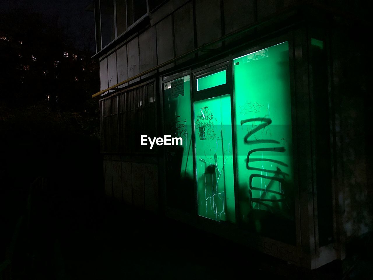 night, architecture, built structure, green color, illuminated, building exterior, no people, text, communication, wall - building feature, building, window, glass - material, western script, dark, outdoors, open, reflection, door