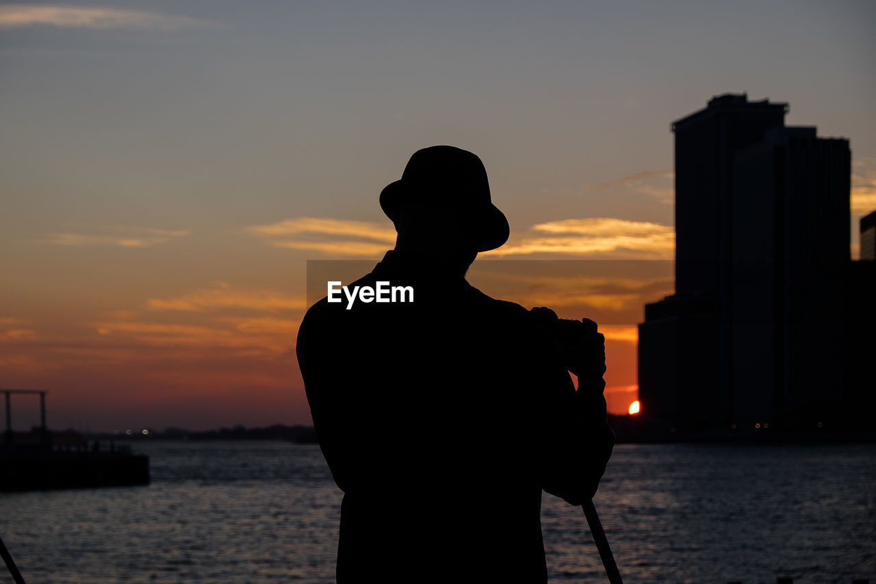 Rear view of man standing against sea during sunset
