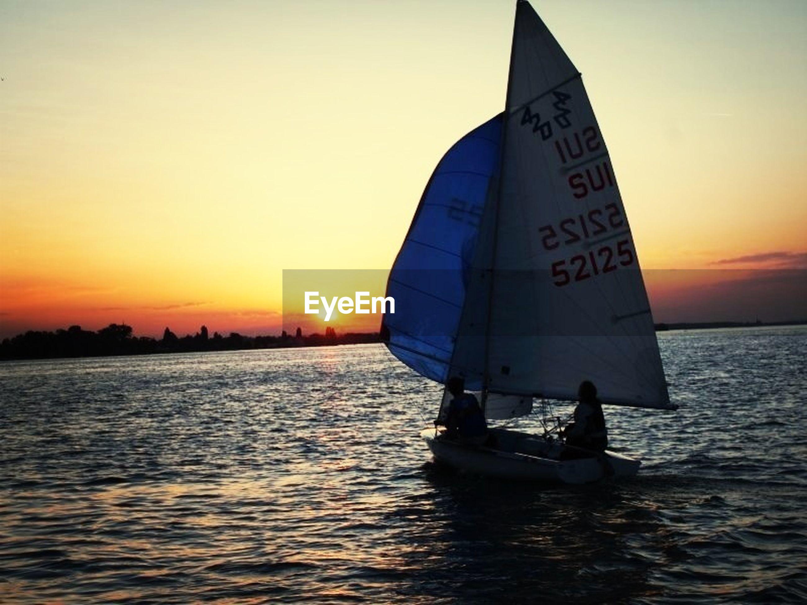 sunset, sea, water, transportation, nautical vessel, mode of transport, waterfront, boat, sky, orange color, horizon over water, sailing, rippled, scenics, men, travel, sun, silhouette