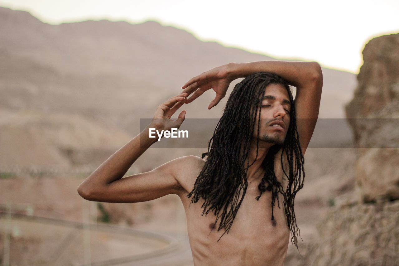 Shirtless man with eyes closed standing against mountains