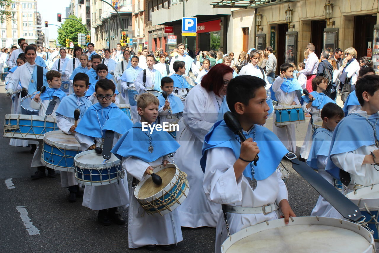 large group of people, musical instrument, real people, music, marching band, drum - percussion instrument, musician, arts culture and entertainment, togetherness, traditional festival, parade, men, celebration, day, standing, performance, women, boys, drummer, outdoors, teamwork, people