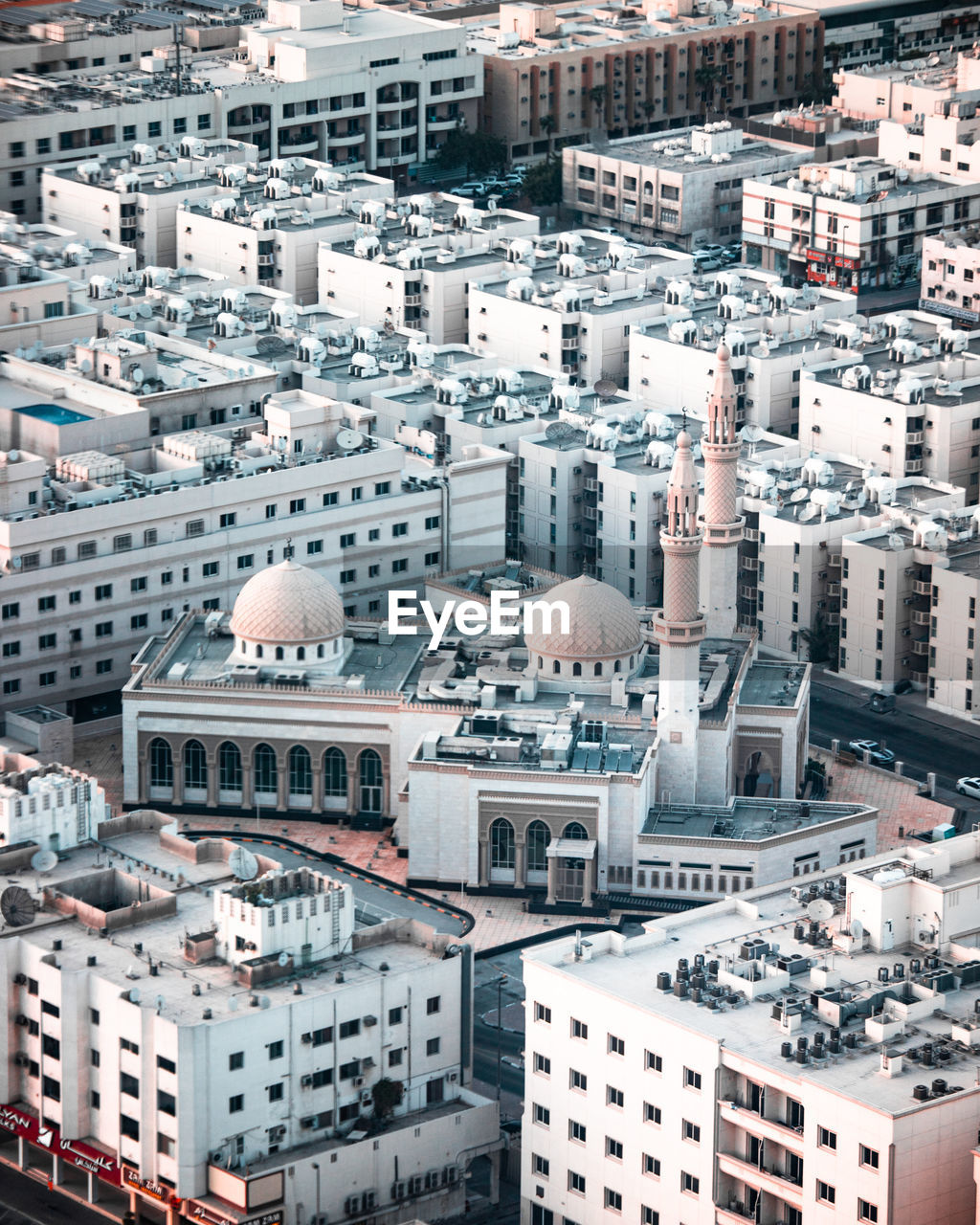 A white mosque in an urban city surrounded by apartment buildings, with the dome and minaret