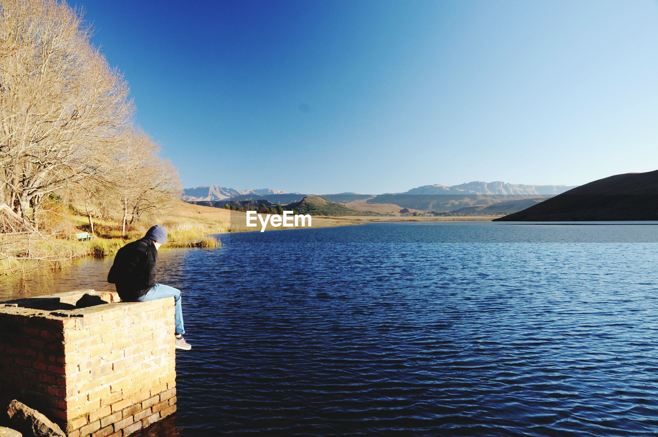 Man sitting on brick structure by lake against blue sky