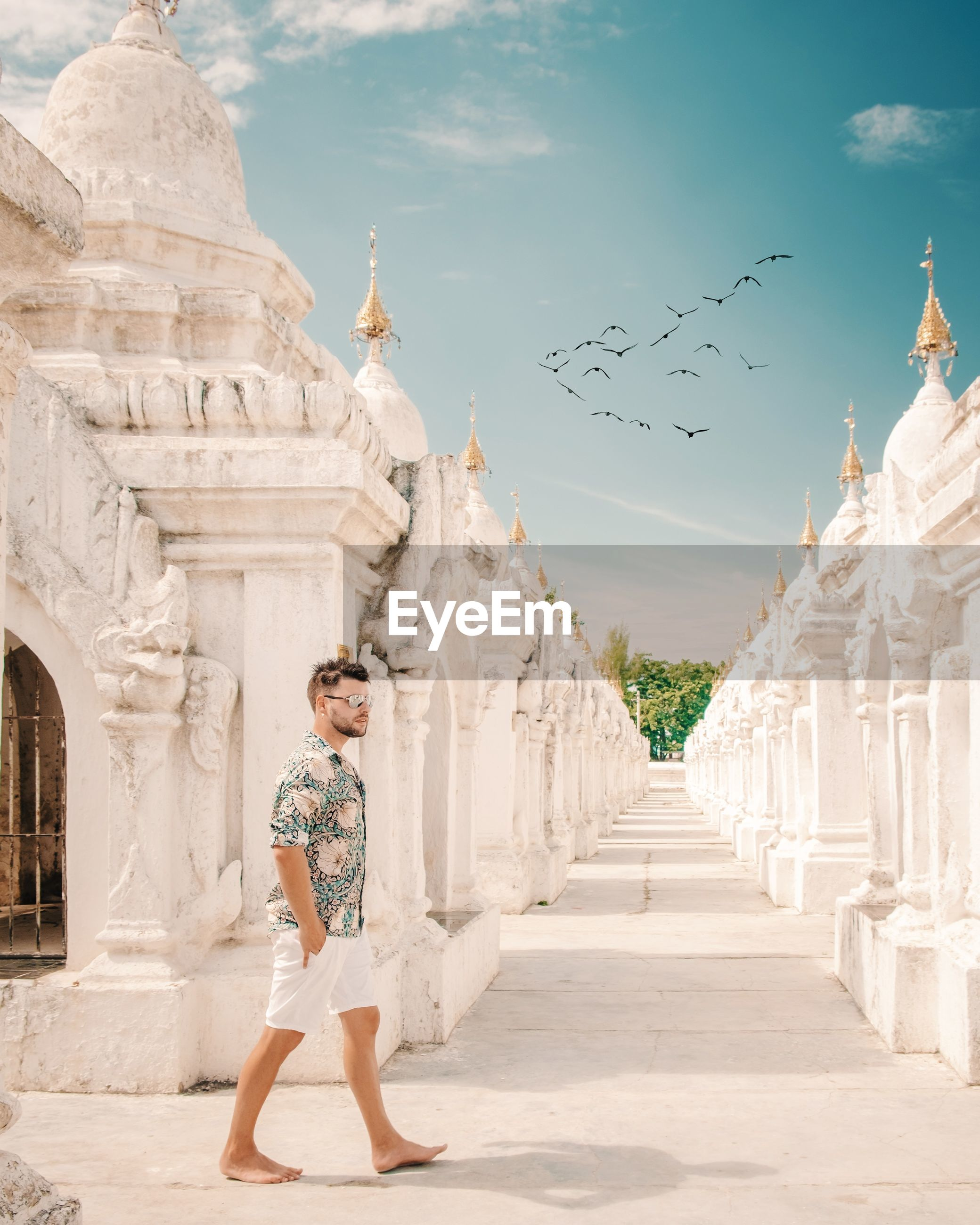 Side view of handsome man walking by stupa